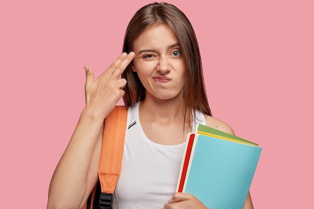 Unbeeindruckter schöner student, der gegen die rosa wand aufwirft