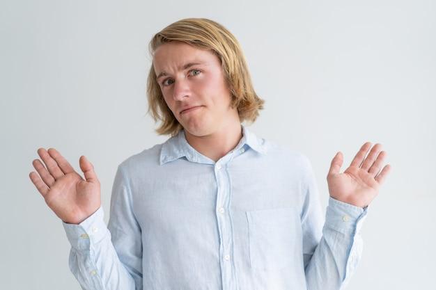Unbefriedigter junger mann, der oben hände wirft und kamera betrachtet