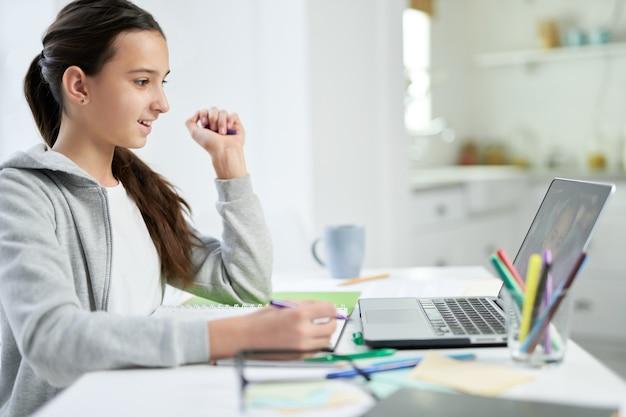 Unbegrenztes lernen fröhliches lateinisches teenager-mädchen, das auf den laptop-bildschirm schaut und ihr zuhört