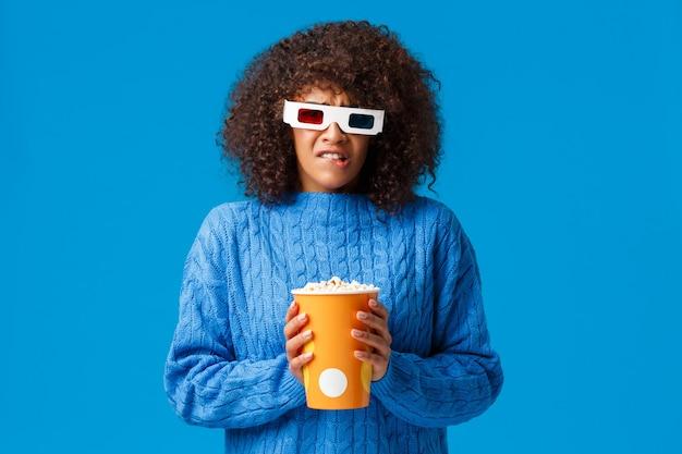 Unbehagliche und traurige niedliche afroamerikanische frau mit afro-haarschnitt, die lieblingscharakter beobachtet, der im film stirbt, verärgert und verzweifelt verzieht das gesicht