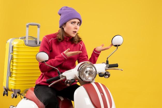 Unbehagliches junges mädchen der vorderansicht auf moped, das auf etwas zeigt