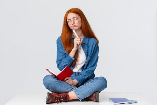 Unbehagliches und trauriges, düsteres junges mädchen gezwungen zu lernen und hausaufgaben vorzubereiten, während freunde feiern, auf dem boden mit gekreuzten beinen sitzen, notizbuch halten und traurig träumen, weiße wand