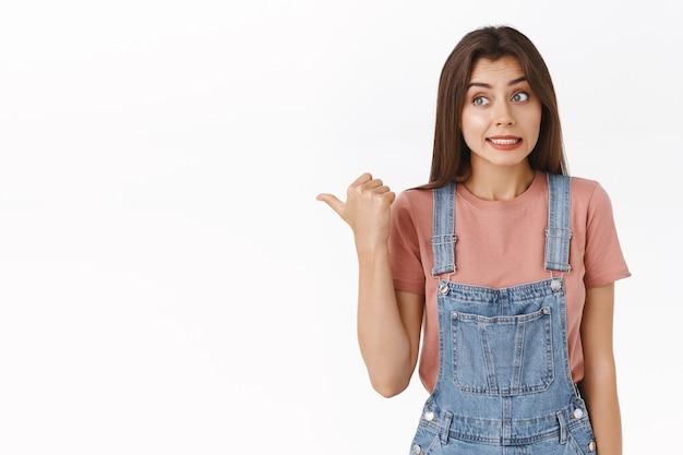 Unbeholfene und leicht besorgte süße brünette frau in overalls, t-shirt, daumen nach links zeigend, zähne zusammenbeißen und verlegen lächeln, als sie etwas flüstern oder andeuten, weißer hintergrund