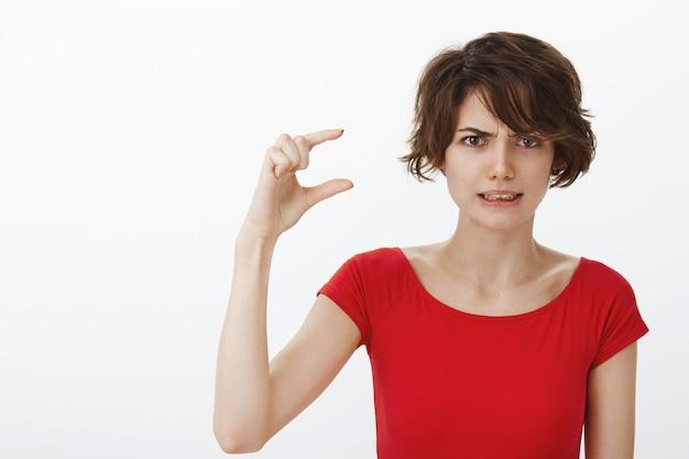 Unbeholfene und unzufriedene frau zucken zusammen und zeigen etwas kleines, beschweren sich über etwas zu weniges