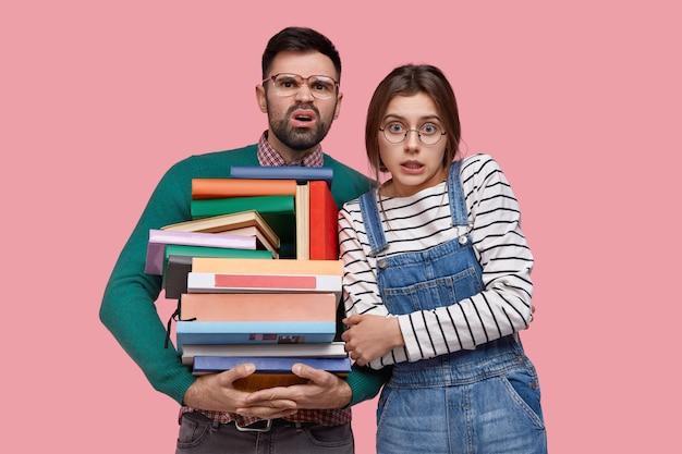 Unbeholfener unrasierter junger mann runzelt die stirn, trägt eine große quadratische brille, trägt viele lehrbücher, junge europäerin hält die hände über der brust gekreuzt