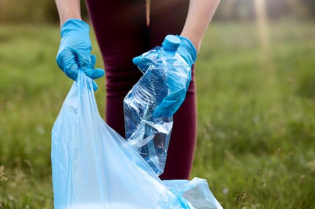 Unbekannte frau, die lässige hosen und latexhandschuhe trägt, die müll zum müllsack aufheben, gebrauchte plastikflasche in der hand halten, sich um den planeten kümmert und wiese aufräumt.
