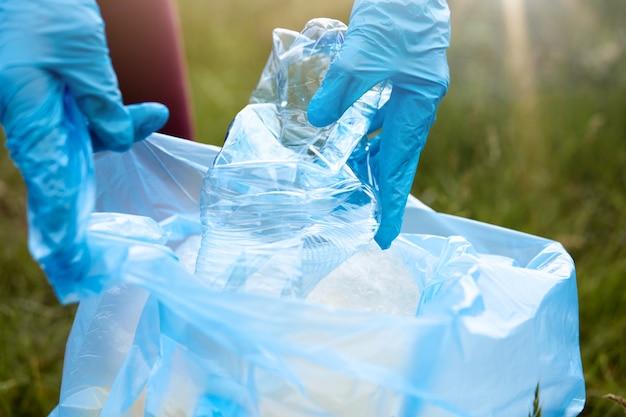 Unbekannte frau, die müll auf dem boden aufnimmt. weibliche freiwillige, die wiesenbereich reinigen, dame in blauen handschuhen legt plastikflasche in müllsack, leute kümmern sich um umwelt.