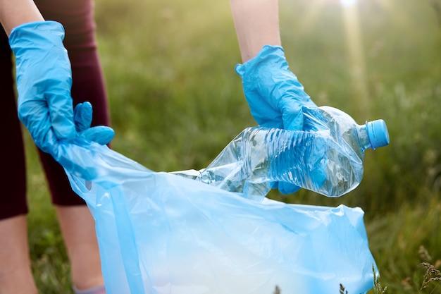 Unbekannte frau, die trash-tag-herausforderung in der wiese tut. frau, die feldbereich aufräumt, latexhandschuhe in plastikflasche vom boden aufhebt, kümmert sich um ökologie.