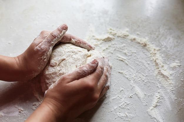 Unbekannte weibliche hände, die teig für gebäck machen, genug mehl auf weißem tisch haben, backfertigkeiten üben, ihre freizeit in der küche verbringen, form von gebäck machen.