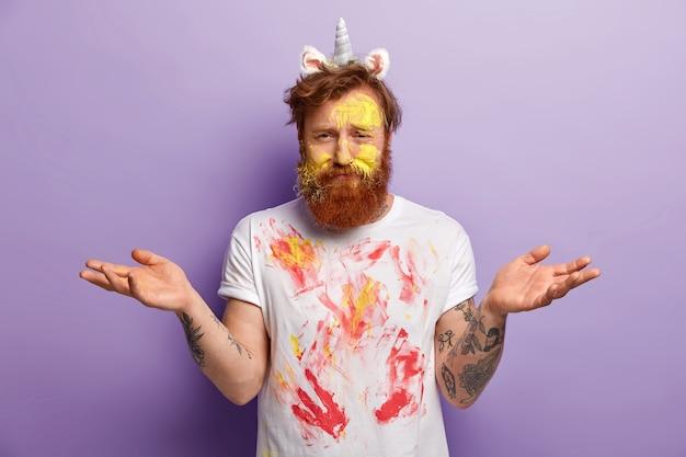 Unbekannter bärtiger junger mann, der mit bunten aquarellen schmutzig ist, hände mit unentschlossenem ausdruck ausbreitet, einhornhorn und ohren trägt, weißes t-shirt mit flecken hat, isoliert über lila wand