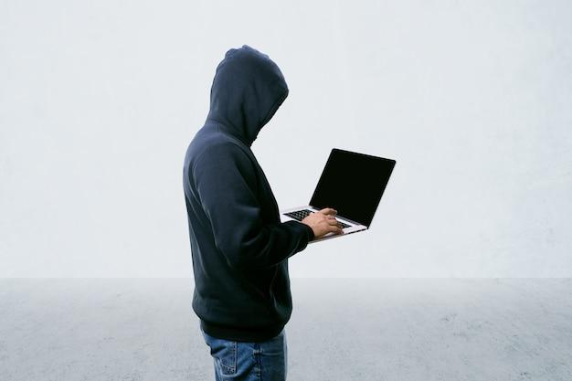 Unbekannter hacker in der haube mit laptop