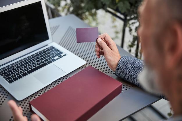 Unbekannter mann, der eine plastikkarte hält, während er seinen laptop geöffnet hat
