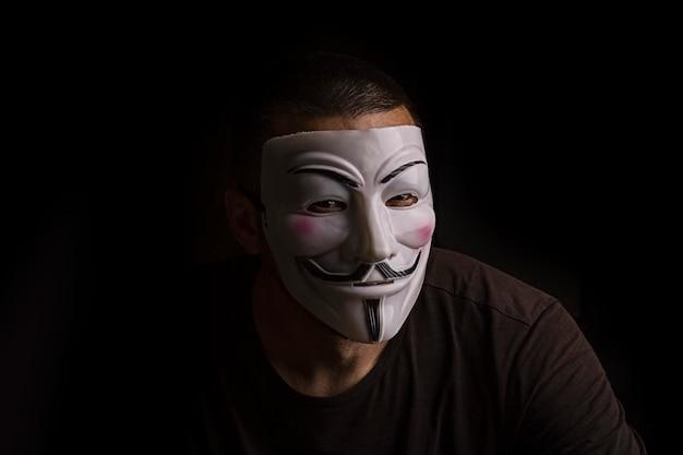 Unbekannter mann mit guy-fawkes-maske in einem dunklen raum
