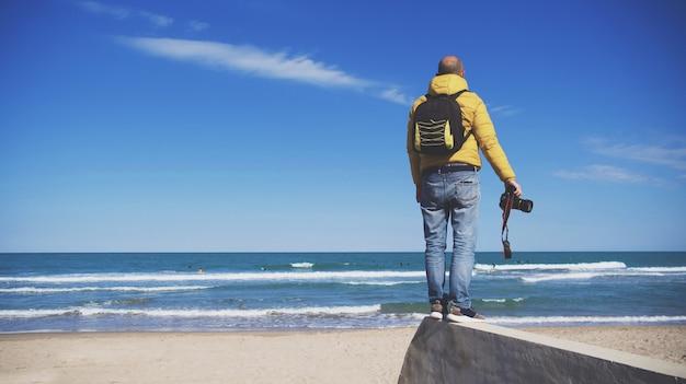 Unbekannter mann mit seiner fotoausrüstung, der an einem sonnigen tag mit blauem himmel fotos am strand macht