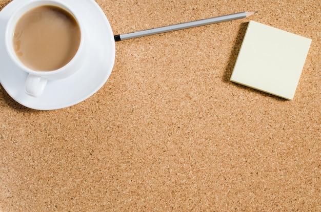 Unbelegte anmerkungen und tasse kaffee auf korkenbrett