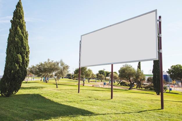 Unbelegte anschlagtafel für reklameanzeige auf grünem gras im garten