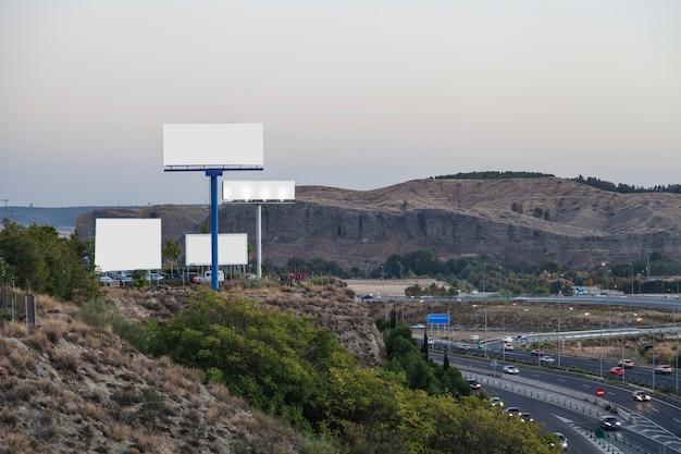 Unbelegte anschlagtafeln für neue reklameanzeige auf berg nahe der landstraße