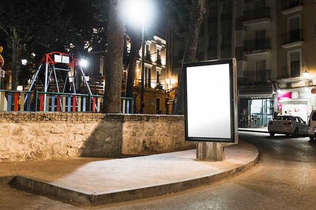 Unbelegte bushaltestelle, die anschlagtafel in der stadt nachts annonciert