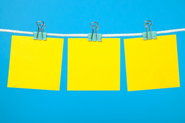 Unbelegte gelbe papieranmerkungen über wäscheleine