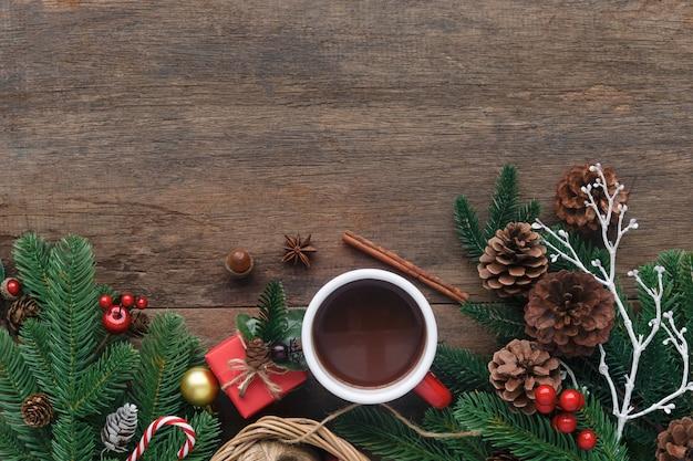 Unbelegte hölzerne planke verzieren mit kieferblatt, kieferkegeln, stechpalmekugeln, zuckerstange und roter schalenschokolade.