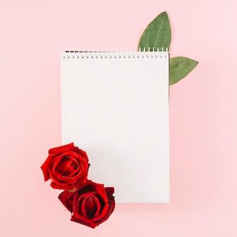 Unbelegter gewundener notizblock verziert mit roten rosen auf rosa hintergrund