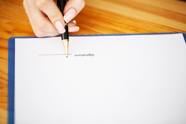 Unbelegtes papier a4 ist mitten in hölzernem schreibtischtisch mit versorgungsmaterialien.