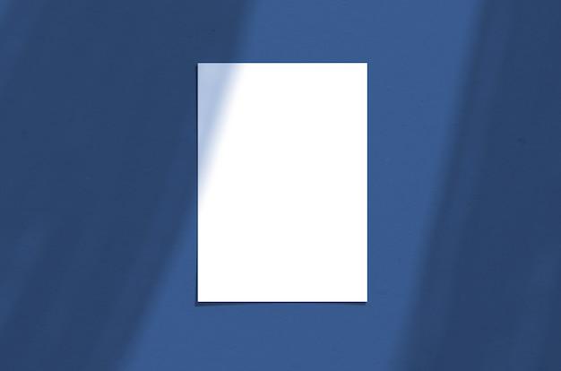 Unbelegtes weißes vertikales papierblatt 5x7 zoll mit schattenüberlagerung. moderne und stilvolle grußkarte oder hochzeitseinladung verspotten. farbe des jahres 2020 klassisches blau.