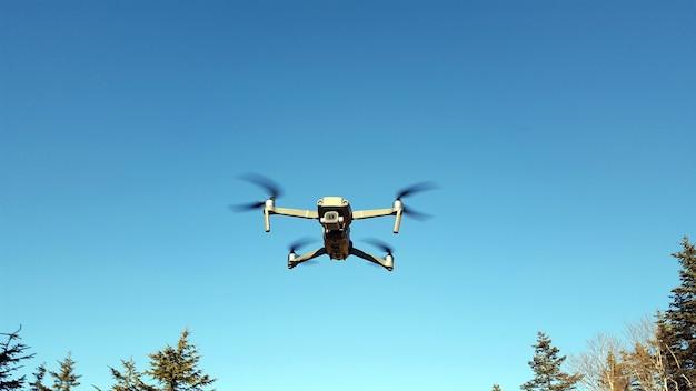 Unbemanntes fluggerät. der quadcopter fliegt in den blauen himmel. moderne technologie . uav.