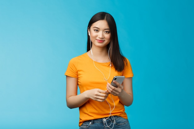 Unbeschwerte, attraktive, angenehme, zarte asiatische stadtfrau trägt kopfhörer, hört musik über kopfhörer, hält smartphone, lächelt erfreut, fand ein tolles neues lied, steht auf blauem hintergrund.