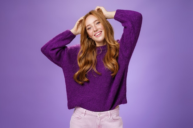 Unbeschwerte, fröhliche und coole, stylische rothaarige studentin in lila, warmem pullover, die ferien genießt, sich dehnen, hände in der nähe des kopfes halten, kippen und glücklich lächeln, sich vor violettem hintergrund entspannen.