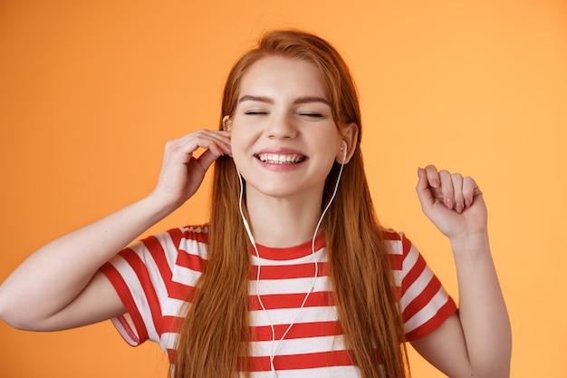 Unbeschwerte glückliche rothaarige frau legte kopfhörer lächelnd erfreut anhören lieblingslied schließen augen entspannt ...