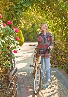 Unbeschwerte junge frau im trendigen vintage-pullover oder pullover in der nähe des fahrrads. verträumtes mädchen mit blonden haaren in strickpullover. hallo herbst tschüss sommer. herbstfrau. glückliches mädchen auf herbstspaziergang.