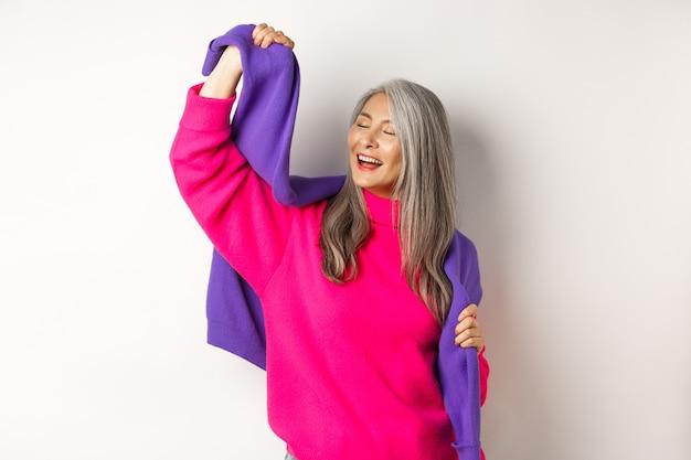 Unbeschwerte koreanische ältere frau im rosa pullover, die mit sweatshirt auf den schultern tanzt und lächelt, glücklich auf weißem hintergrund posiert