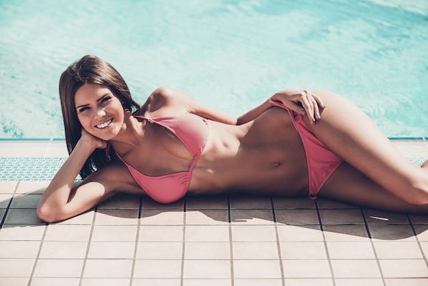 Unbeschwerte sommerzeit. in voller länge der schönen jungen lächelnden frau im bikini, die am pool liegt und kamera betrachtet