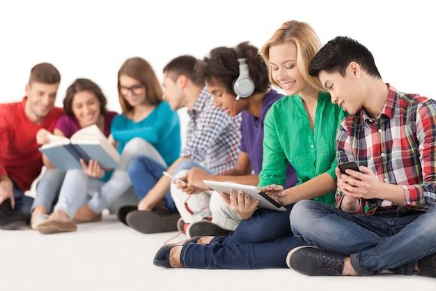 Unbeschwerte teenager. gruppe multiethnischer studenten, die zeit zusammen verbringen, während sie isoliert auf weiß sitzen