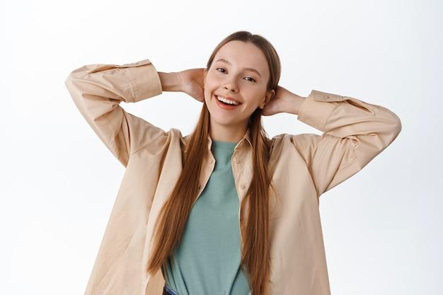 Unbeschwerte teenager-studentin, die hände hinter dem kopf hält, beim entspannen lächelt, sich ausruht, freizeit hat, die freizeit am wochenende genießt, über der weißen wand steht?
