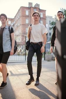 Unbeschwerte teenager verbringen nach dem unterricht zeit miteinander. moderner urbaner straßenjugendlebensstil. freizeit- und freundschaftskonzept