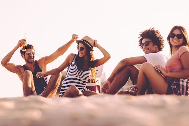 Unbeschwerte zeit mit freunden genießen. fröhliche junge leute verbringen schöne zeit miteinander, während sie am strand sitzen und bier trinken