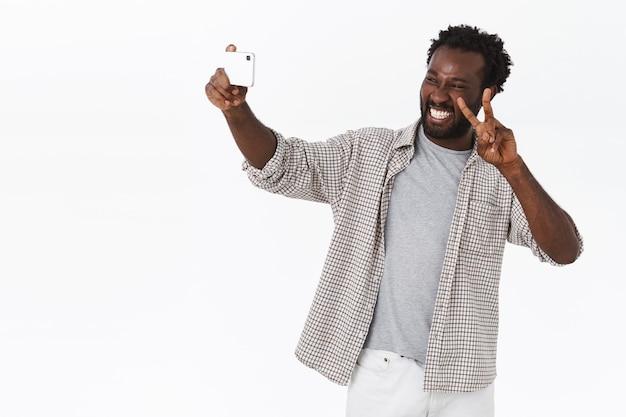 Unbeschwerter afroamerikanischer bärtiger kerl reist ins ausland und macht selfies im urlaub