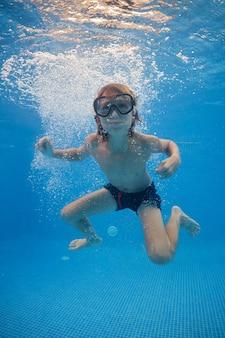 Unbeschwerter junge, der im pool mit klarem wasser unter wasser schwimmt