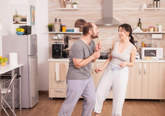 Unbeschwertes, glückliches und fröhliches paar, das am morgen in der küche tanzt und singt. fröhlicher ehemann und ehefrau lachen, singen, tanzen, hören nachdenklich, leben glücklich und sorgenfrei. positive menschen