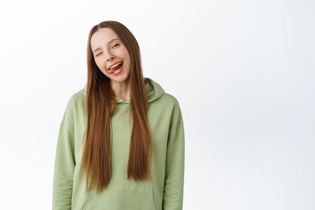 Unbeschwertes schönes tausendjähriges mädchen zeigt zunge, lächelt mit weißen perfekten zähnen und zwinkert, steht im hoodie mit positiven emotionen, studiowand