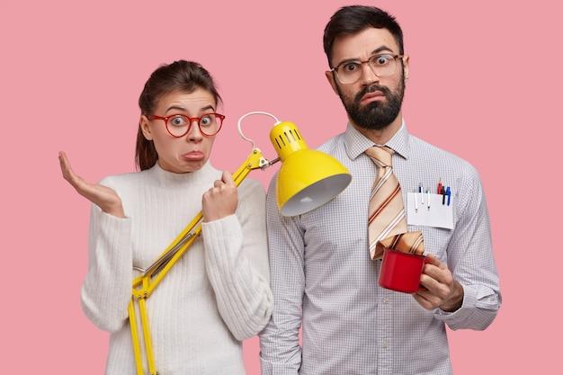 Unbewusst zögernde junge frau und mann haben ahnungslose gesichtsausdrücke, stehen nebeneinander, tragen gelbe schreibtischlampe, tasse getränk