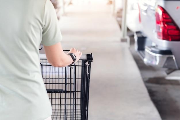 Undeutlich vom handfokus und von selektiven fokus des handfokus halten wagen arar carpark am supermarkt