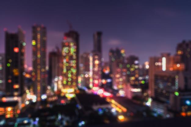 Undeutliche bangkok-nachtansicht mit wolkenkratzer im geschäftsgebiet in bangkok thailand