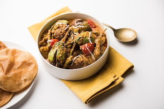 Undhiyu ist ein gemischtes gemüsegericht aus gujarati, eine spezialität aus surat, indien. serviert in einer schüssel mit oder ohne poori