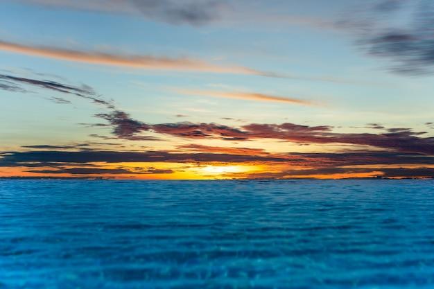 Unendlichkeitsswimmingpool mit sonnenunterganghimmel vover der ozean.