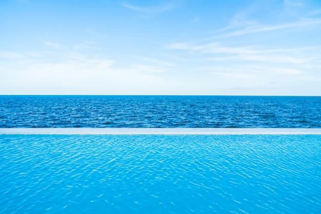 Unendlichkeitswimmingpool mit see- und meerblick auf blauem himmel