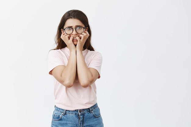 Unentschlossene junge brünette mit brille posiert