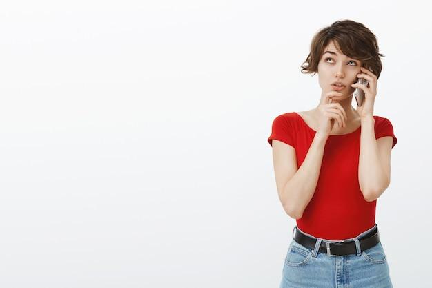 Unentschlossene junge frau, die denkt, während sie am telefon spricht, essen bestellt und wahl trifft